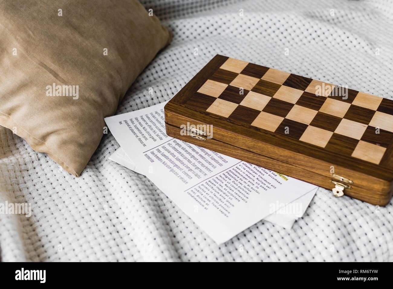 wooden chess board near newspaper on sofa Stock Photo