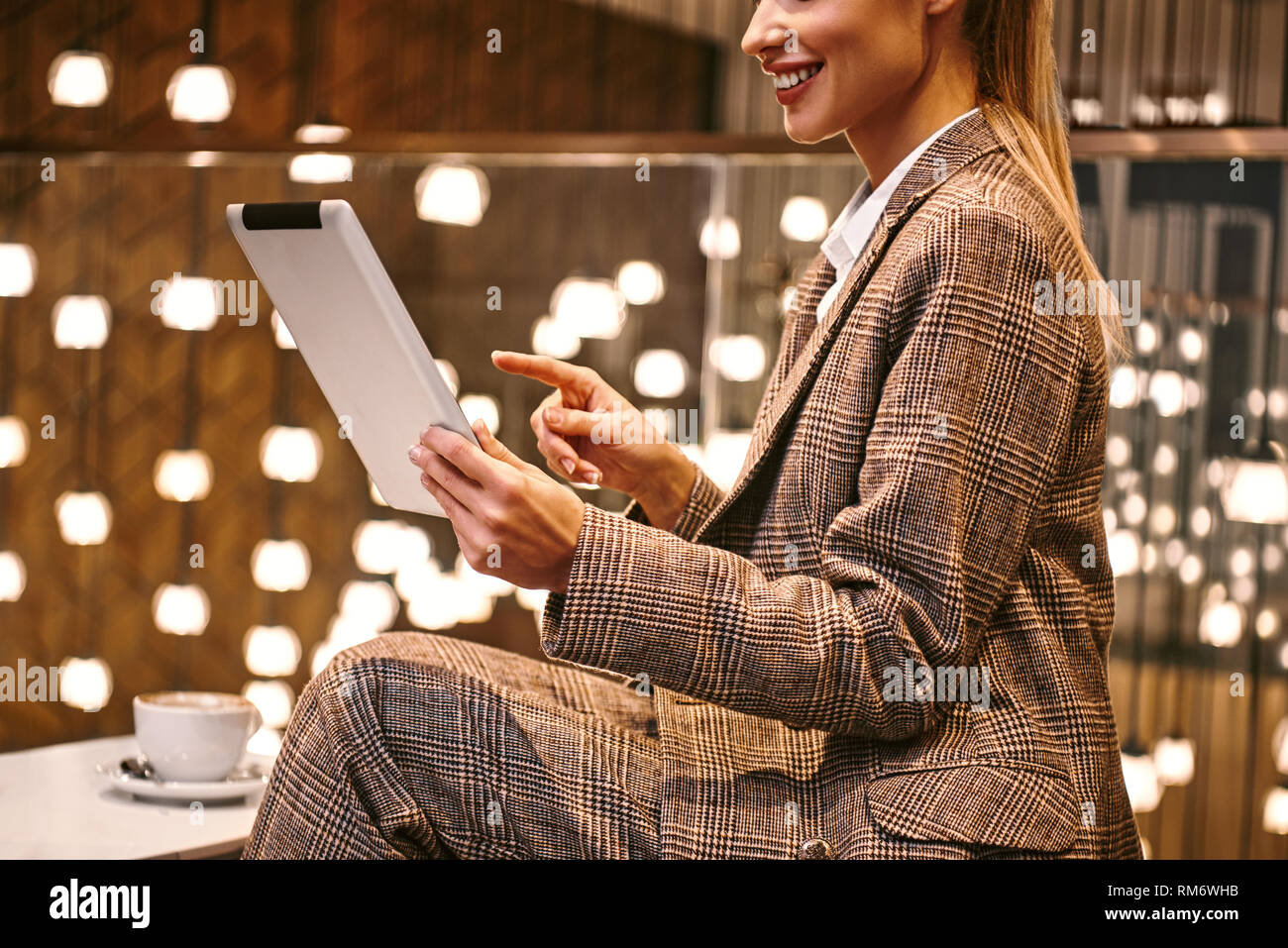 Waiting for business partner. Cropped photo of happy young woman using digital tablet while sitting at hotel restaurant nearby suitcase. Luxury interiour at backbround - Stock Image