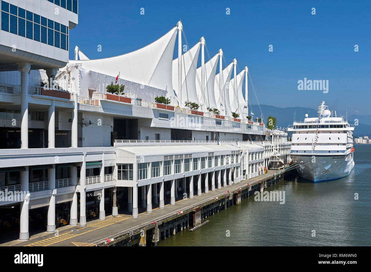 Vancouver, B.C., Canada - July 12, 2012: Canada Place Cruise Terminal at downtown Waterfront with its distinctive white sails, and dogged cruise ship - Stock Image