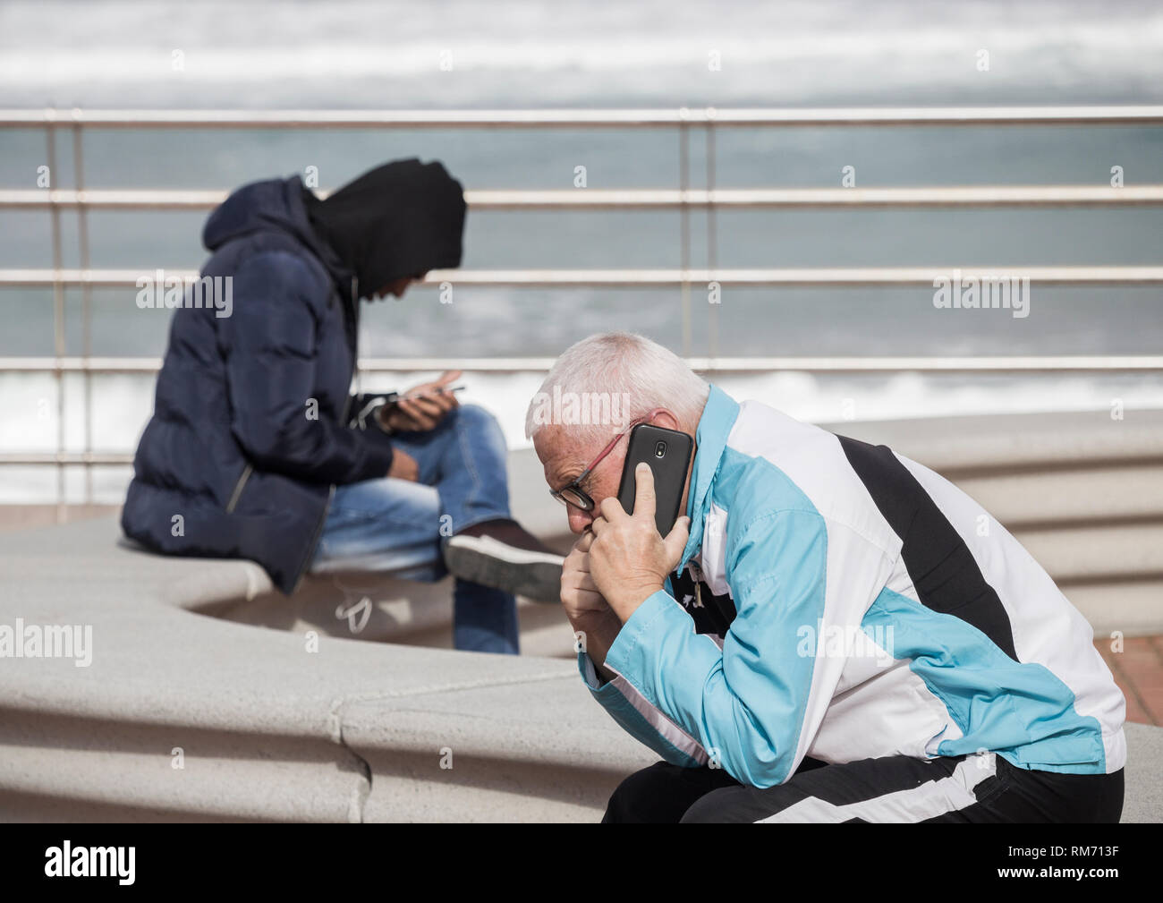 Elderly man and young man sitting on seat oveloooking the sea. Both using mobile phones - Stock Image