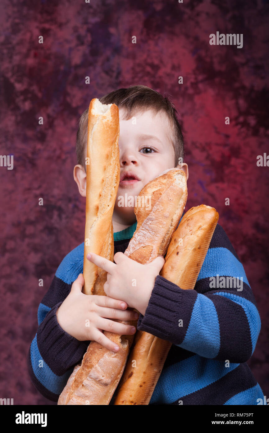 5aa53c706aad5 Cute kid holding French bread against dark red background. Little boy  eating the french baguette