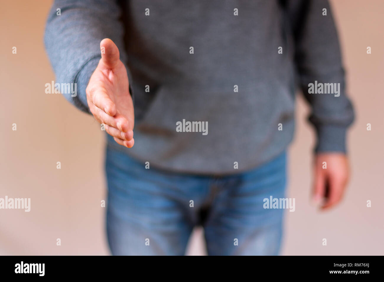 Hand reaching out for a handshake - Stock Image