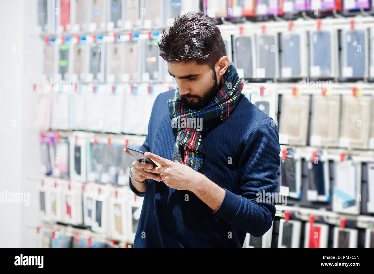 Indian beard man customer buyer at mobile phone store looking on his  smartphone. South asian peoples and technologies concept. Cellphone shop.
