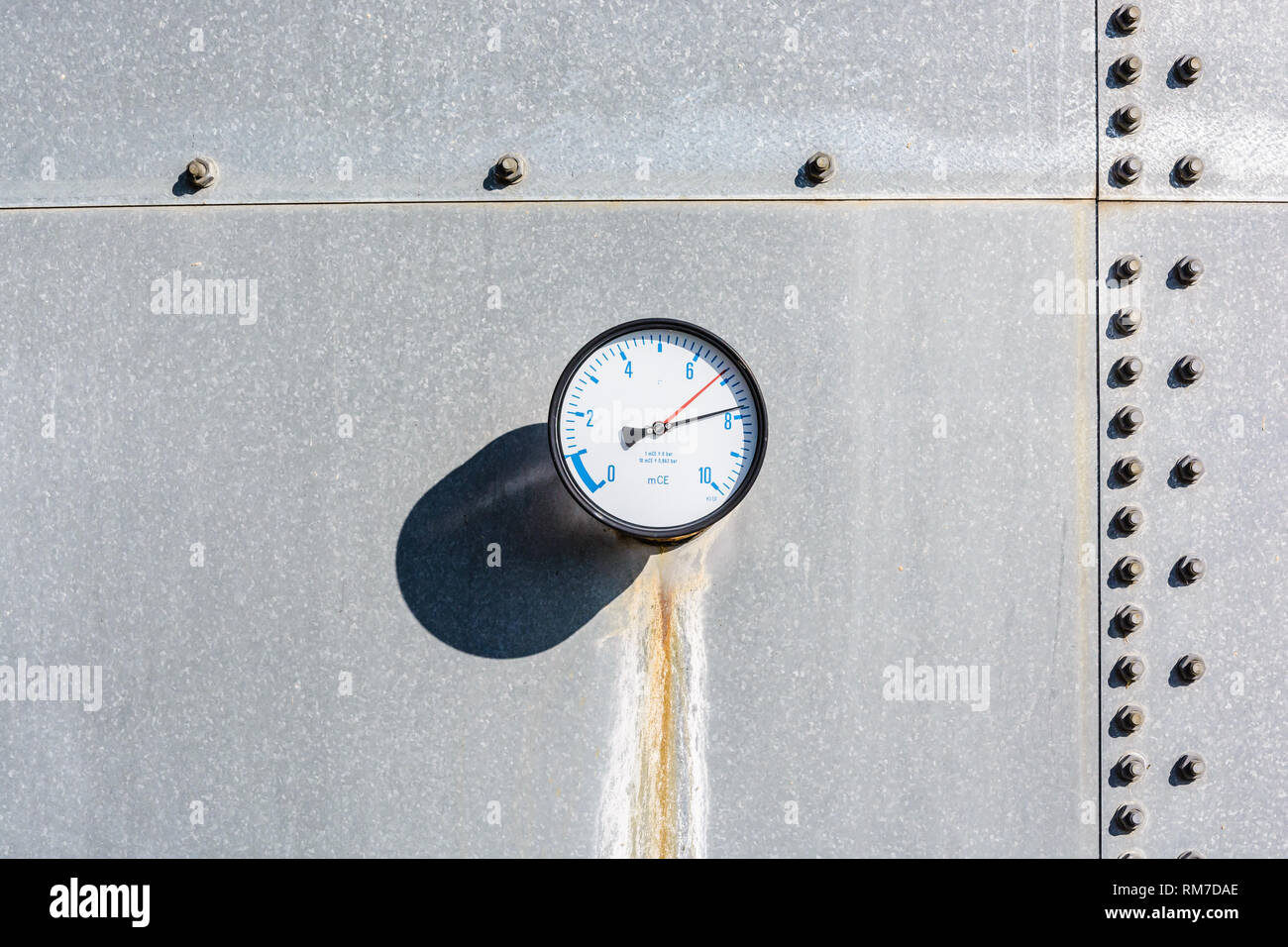 A round gauge with a dry and rusty streak running down below, fitted on the wall of a galvanized steel water tank, with blue figures on a white dial. - Stock Image