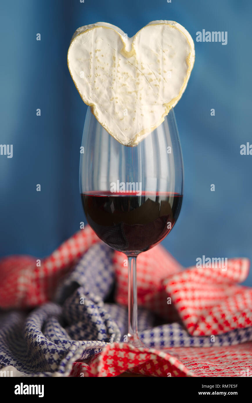 Composition with Neufchatel, Norman cheese (A.O.P.) and glass of wine, on a blue background. - Stock Image