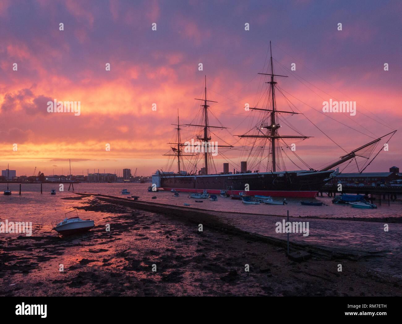 Historic warship HMS Warrior at sunset, Portsmouth Historic Dockyard, England - Stock Image