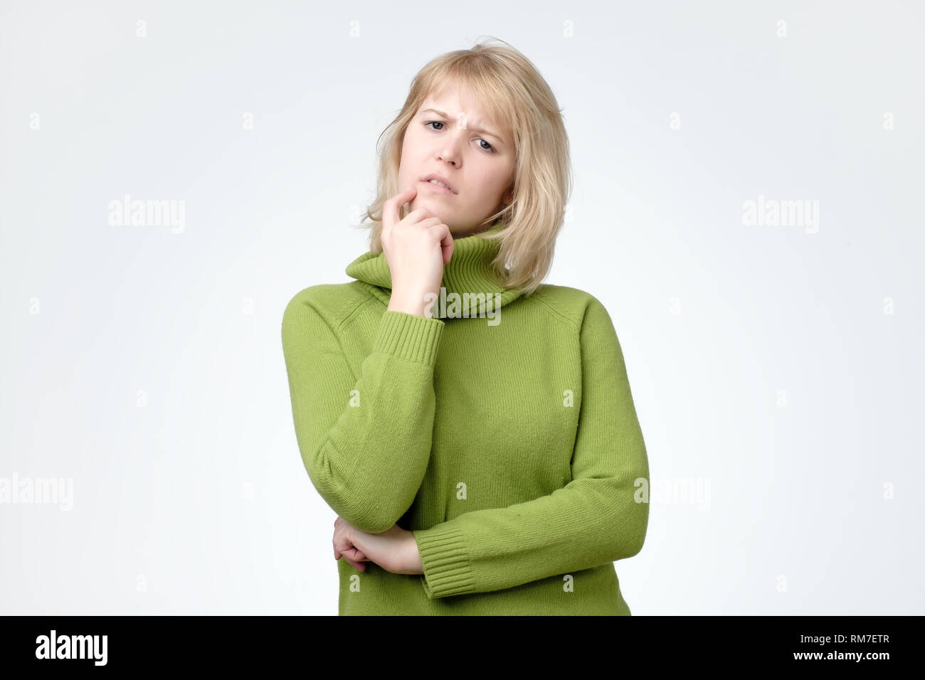 Woman in green sweater making a plan on her holidays. - Stock Image