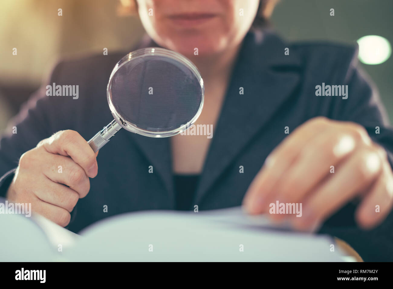 Business corruption audit inspection concept, female inspector using magnifying glass Stock Photo