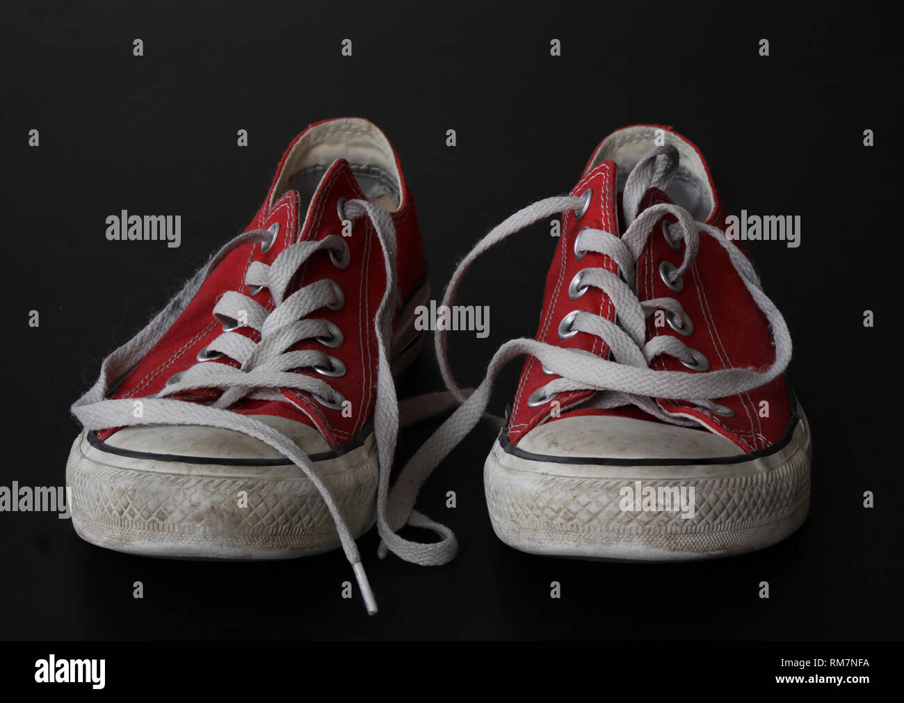Close up of pair of sneakers - red and white vintage worn out shoes - youth hipster shoes on black background - Stock Image
