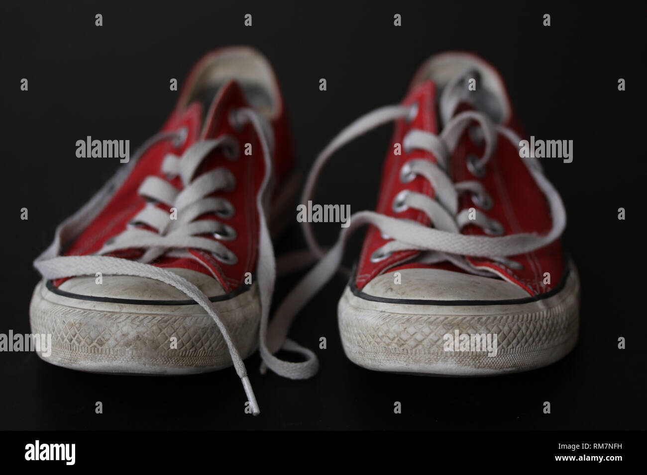 Close up of pair of sneakers - red and white vintage worn out shoes - youth hipster shoes on black background with select focus. - Stock Image