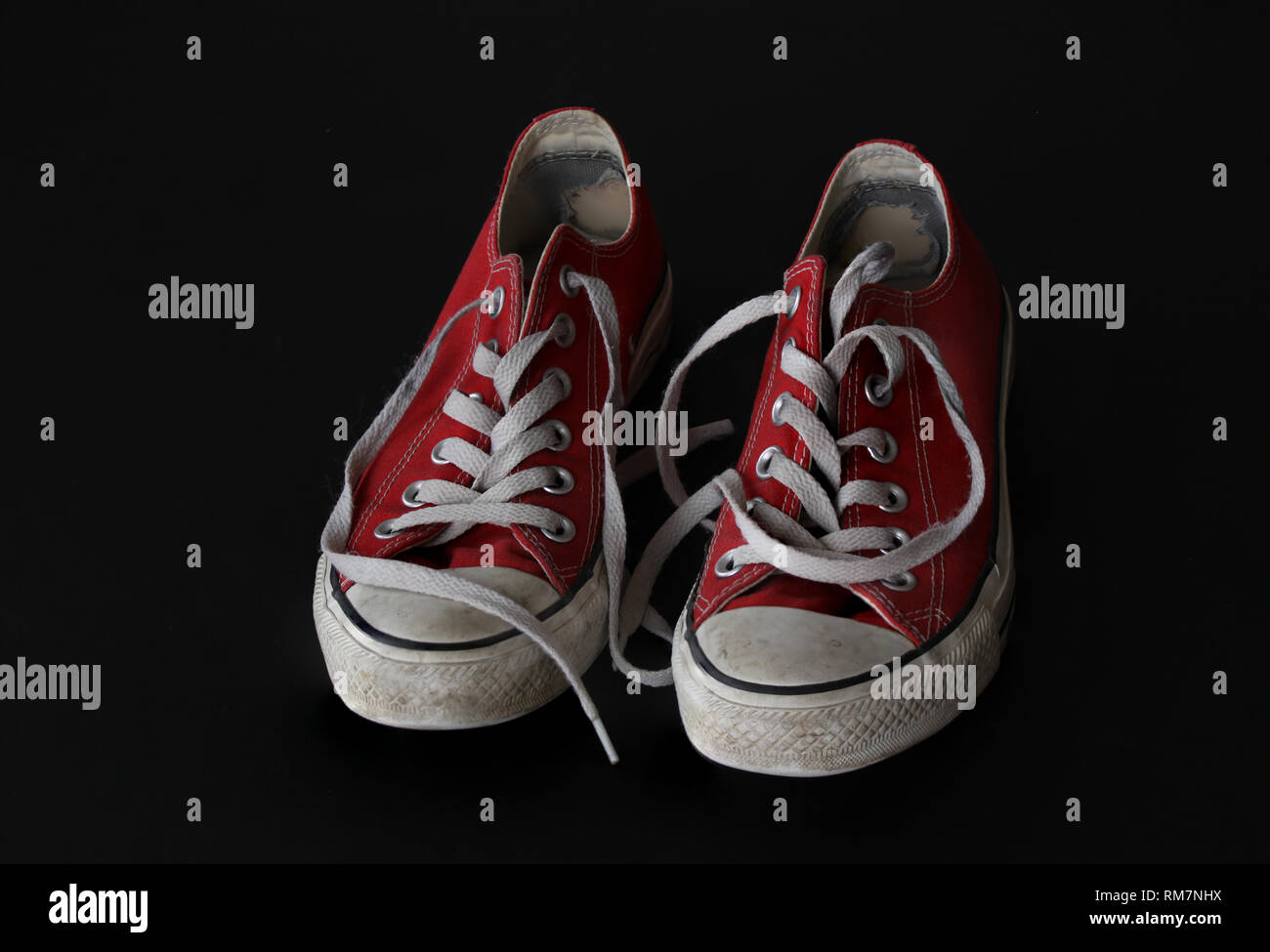 Close up of pair of sneakers - red and white vintage worn out shoes - youth hipster shoes on black background - top view - Stock Image