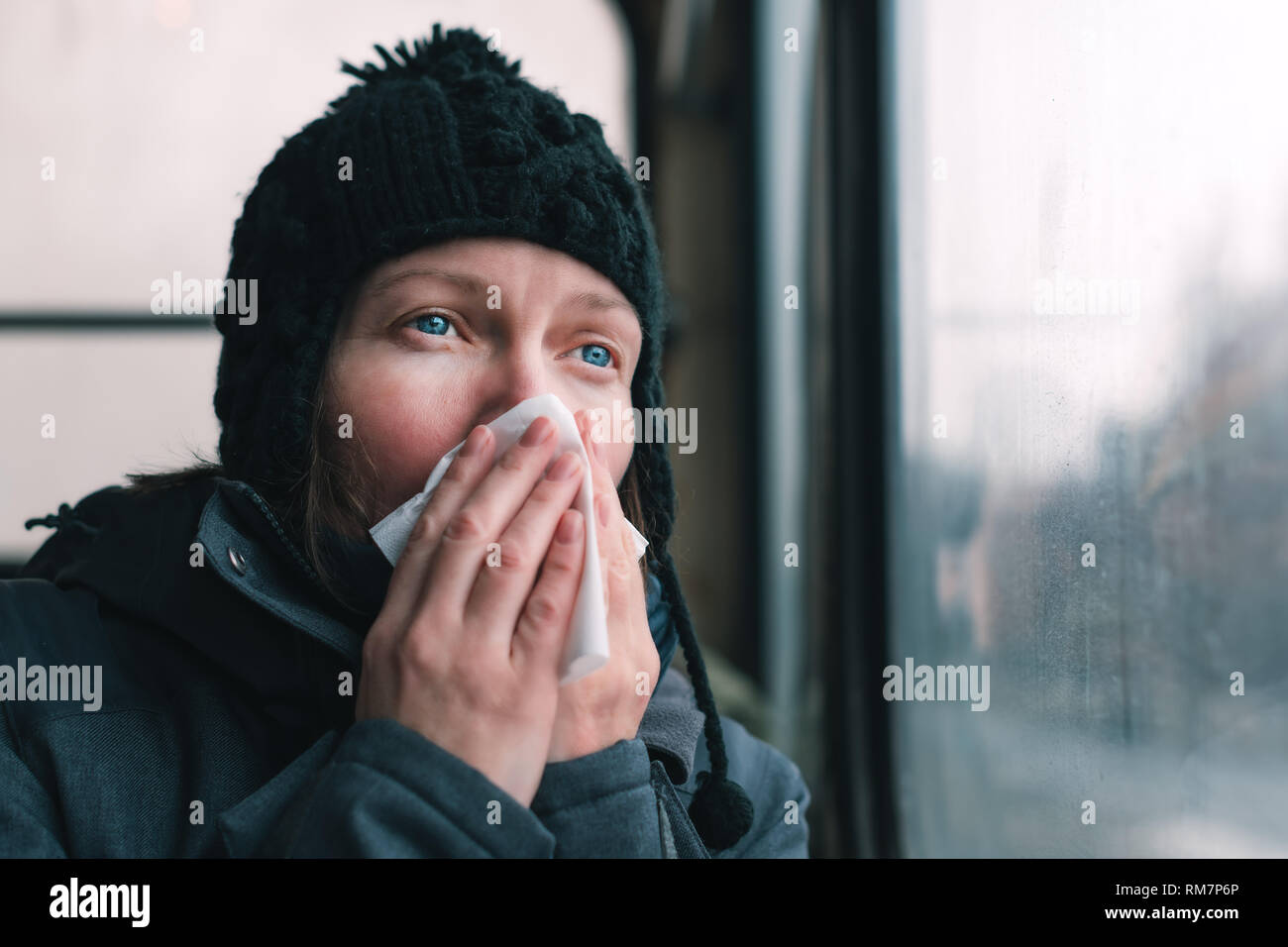 Woman blowing her nose into paper handkerchief on the bus on a cold winter day at the start of the flu season - Stock Image
