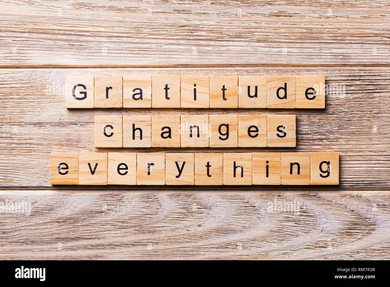 Gratitude changes everything word written on wood block. Gratitude changes everything text on wooden table for your desing, concept. - Stock Image