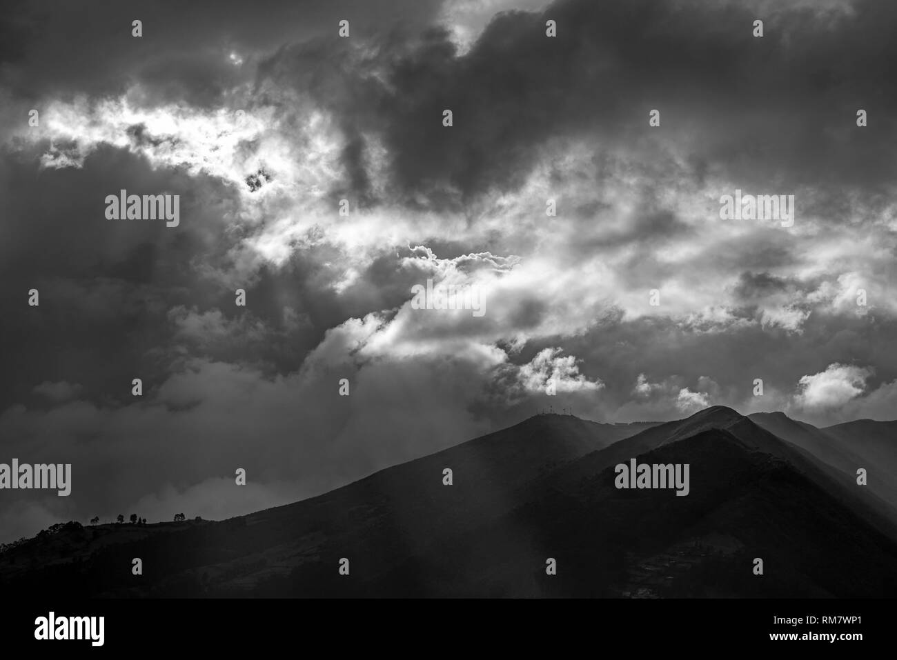 The majestic active Pichincha volcano in the city of Quito at sunset in black and white with a magic sunbeam, Andes mountains, Ecuador. - Stock Image