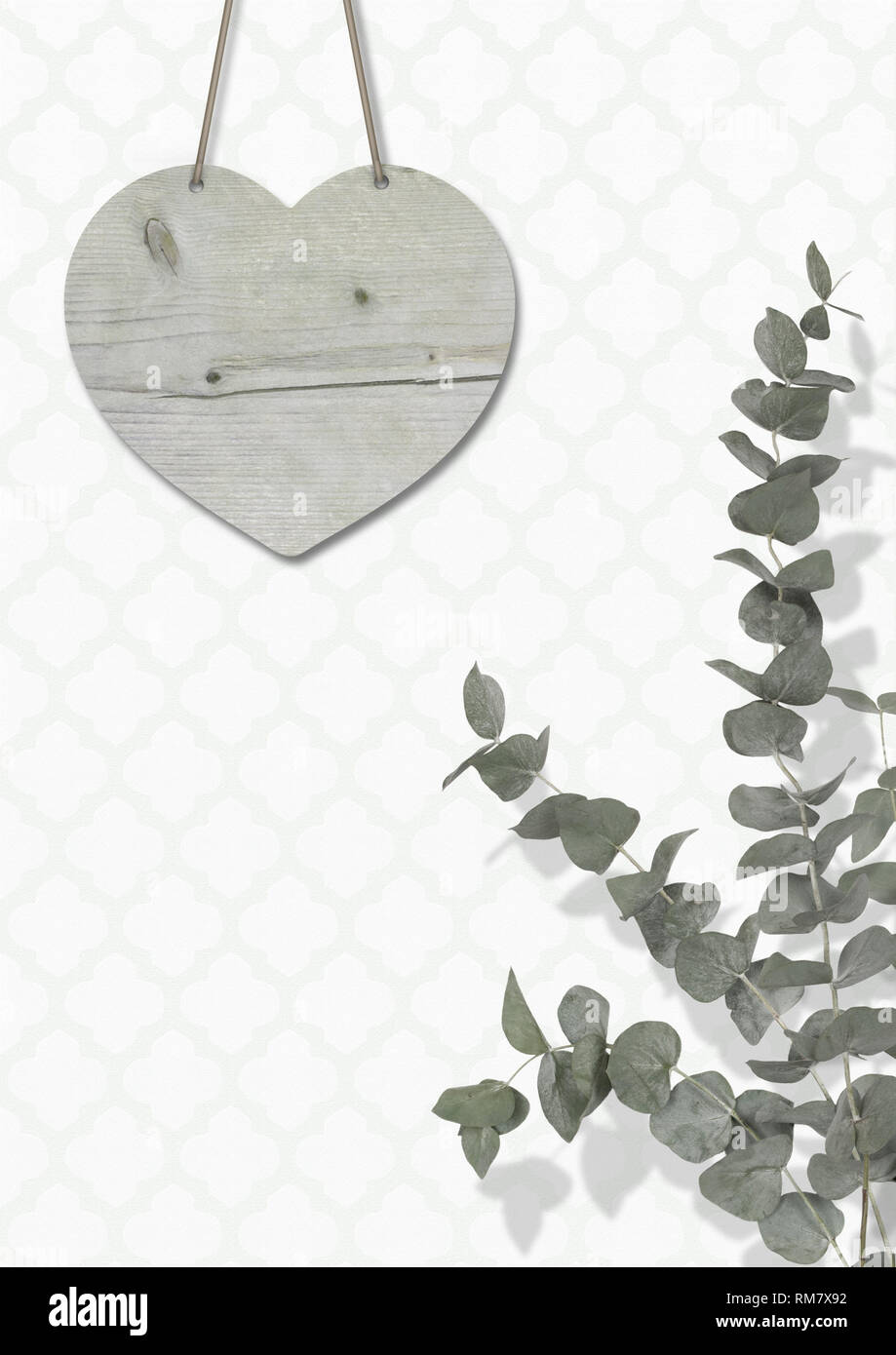 blank weathered wooden heart on wall with moroccan print wallpaper, with Eucalyptus cinerea, interior still life with copy space Stock Photo