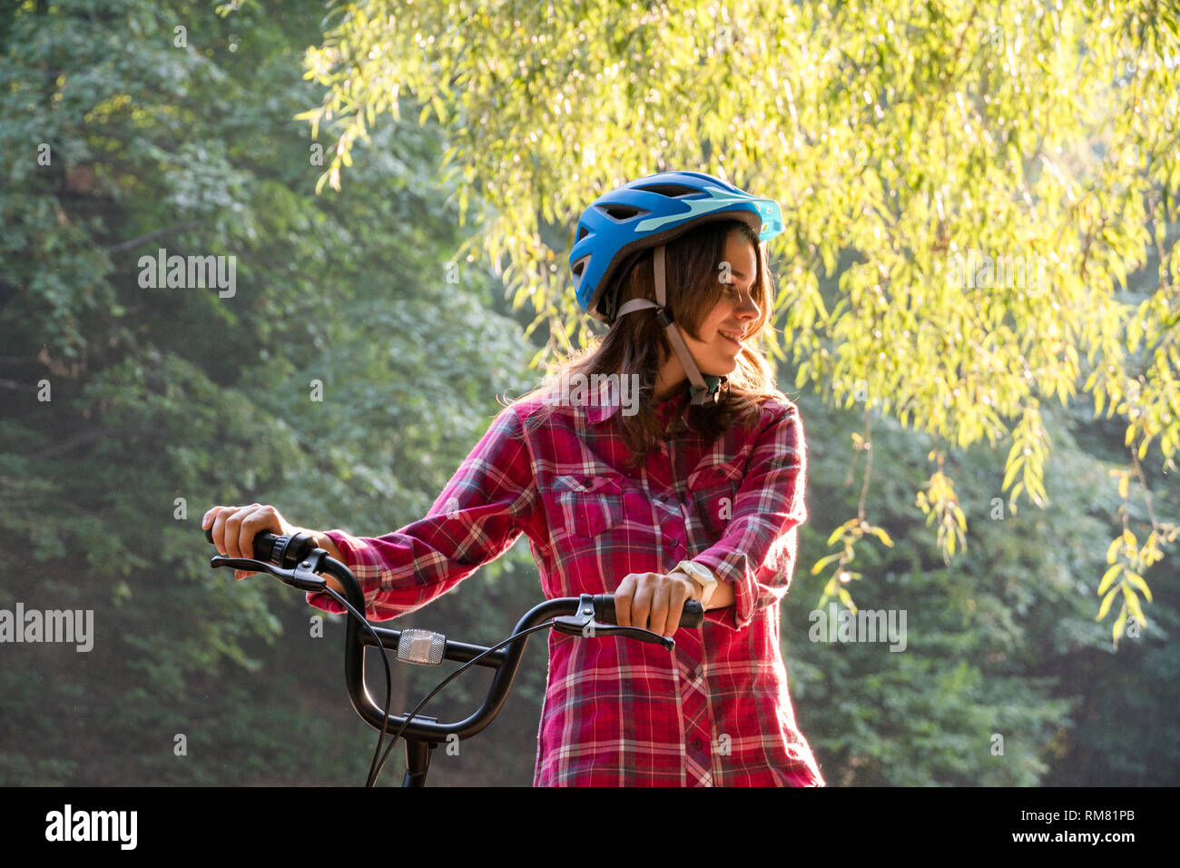 Subject Ecological Mode Of Transport Bicycle Beautiful Young Kasazy Woman Wearing A Blue Helmet And Long Hair Poses Standing Next To An Orange Colore Stock Photo Alamy