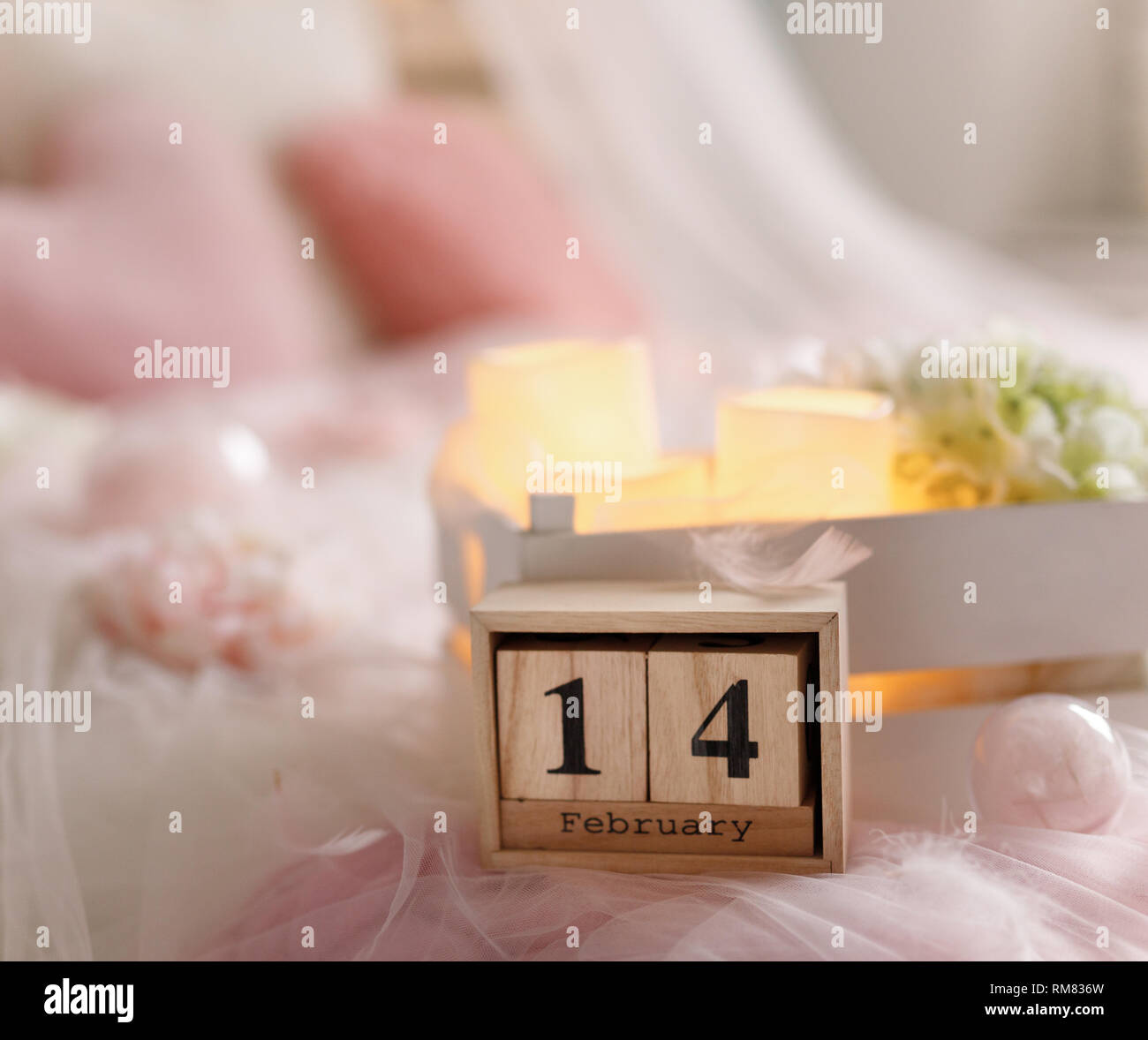 wooden calendar the 14 th of february on the  rose bed - Stock Image