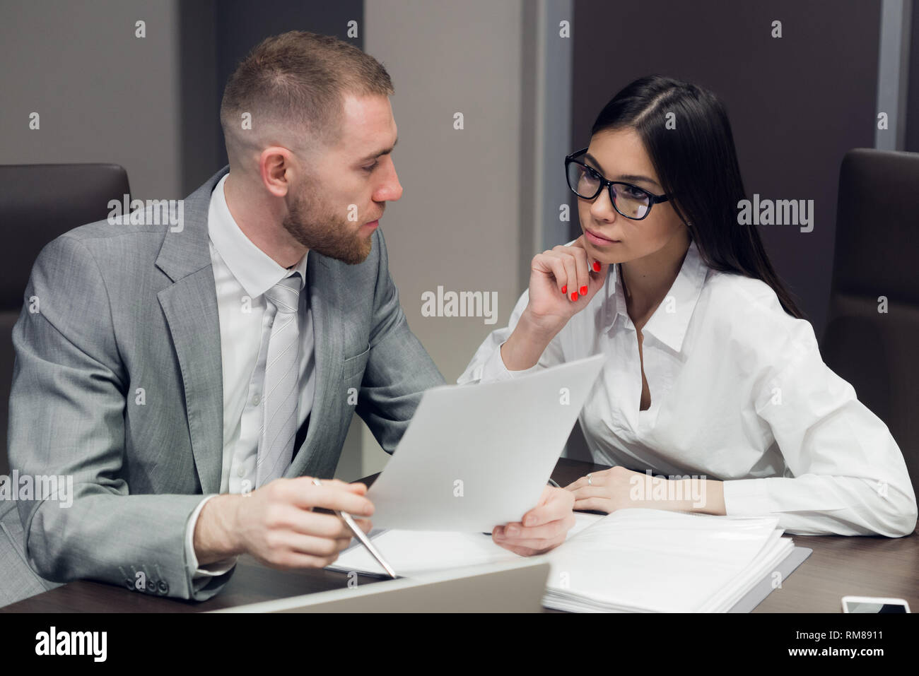 Two young business people discussing work during a business presentation in conference room - Stock Image