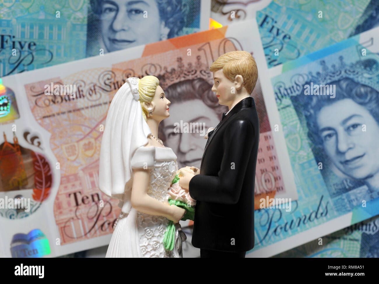 BRIDE AND GROOM FIGURES WITH BRITISH BANKNOTES RE WEDDING COSTS MARRIAGE DIVORCE LAWYERS FIRST TIME HOUSE BUYERS ETC UK - Stock Image