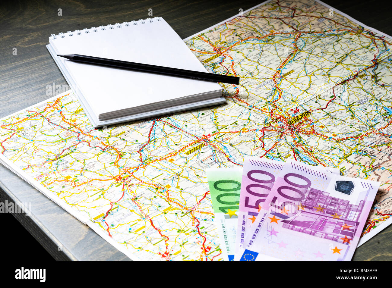 Close up of map, money, blank canvas notepad and pencil. Traveller equipment or set concept. Packing things for travelling. Making plans for travel. - Stock Image