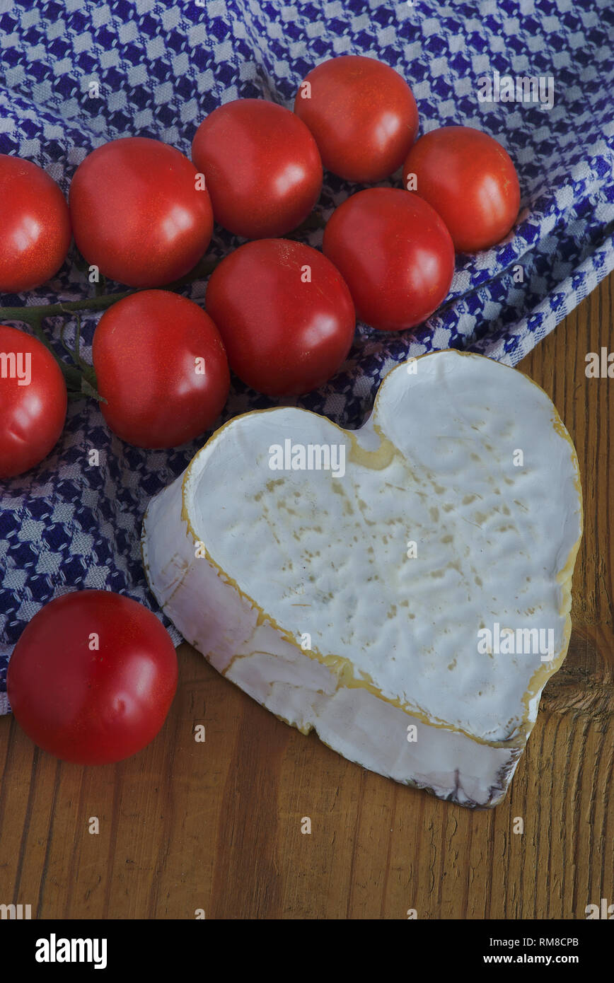 Neufchatel cheese (A.O.P. Normande) and a cluster of cherry tomatoes. Rustic background - Stock Image