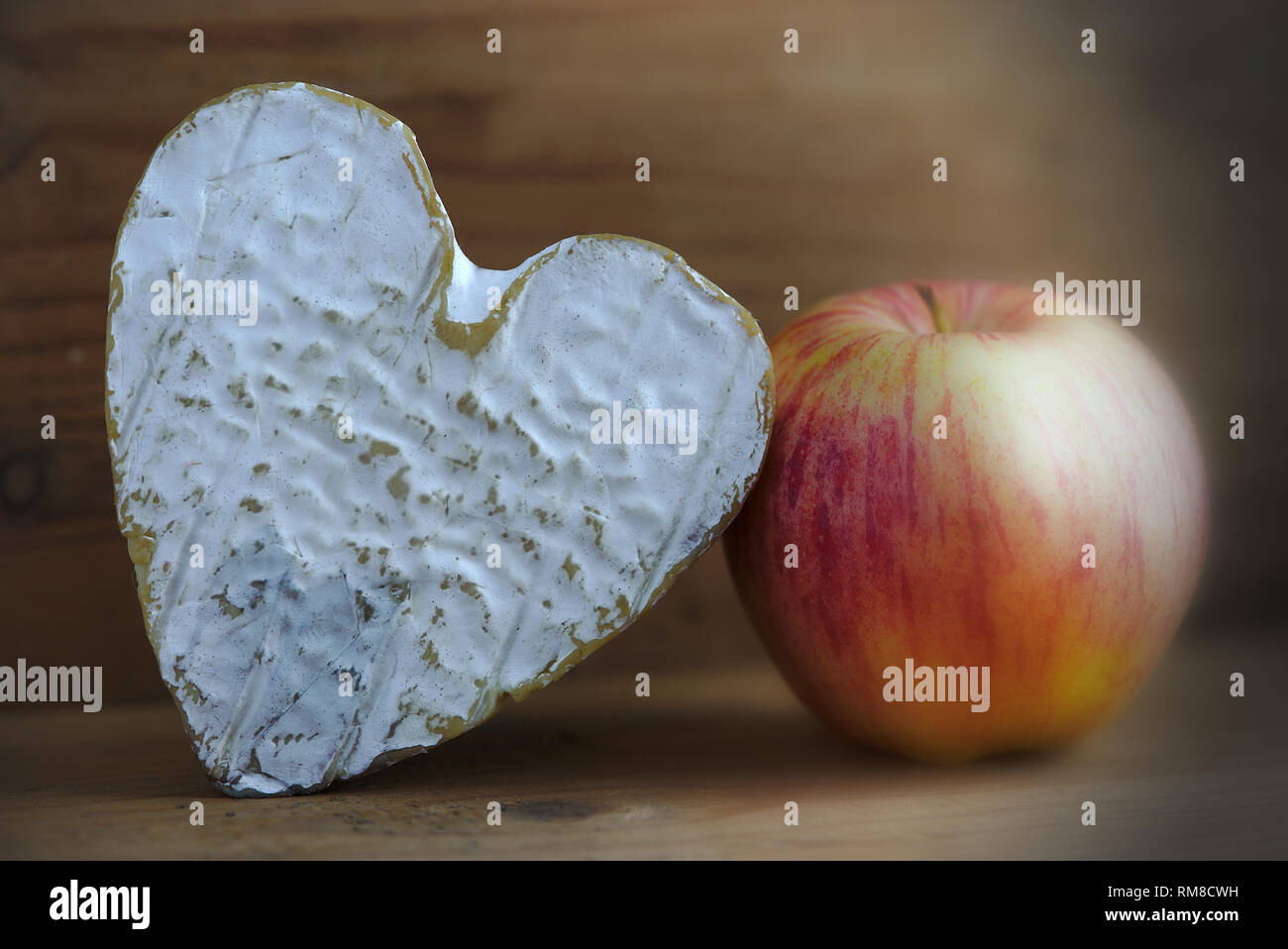 still life with a Norman cheese Neufchatel (A.O.P.) and an apple, on wooden background - Stock Image