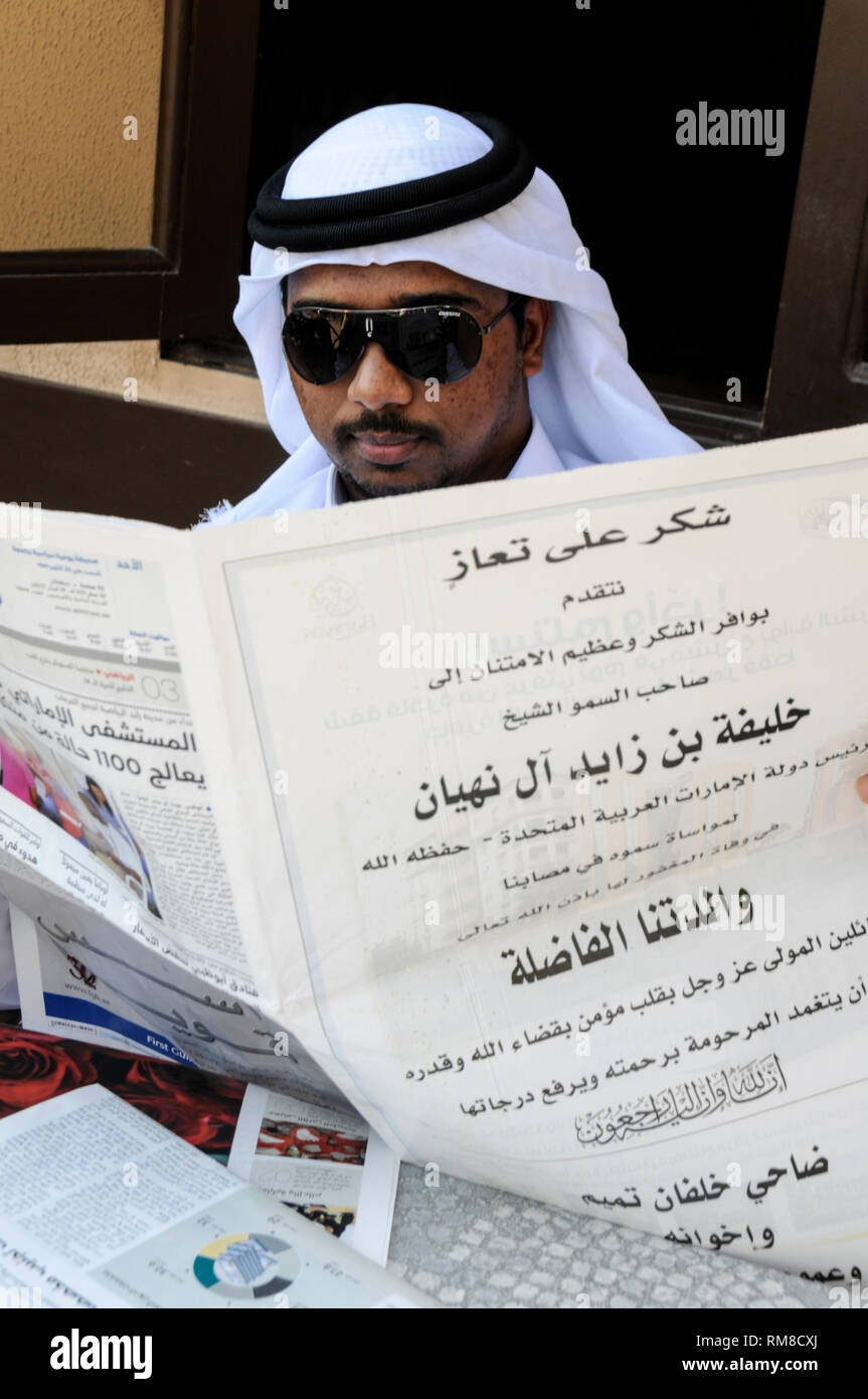 An Emirati man in traditional Arab robes and  a  plain white keffiyeh, relaxing, reading his daily newspaper in Dubai in the United Emirates, (UAE). Stock Photo