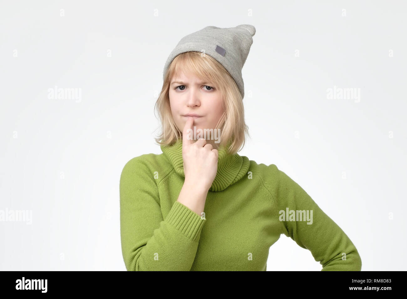 Blonde female wearing green sweater with puzzled expression, keeps finger on lips - Stock Image