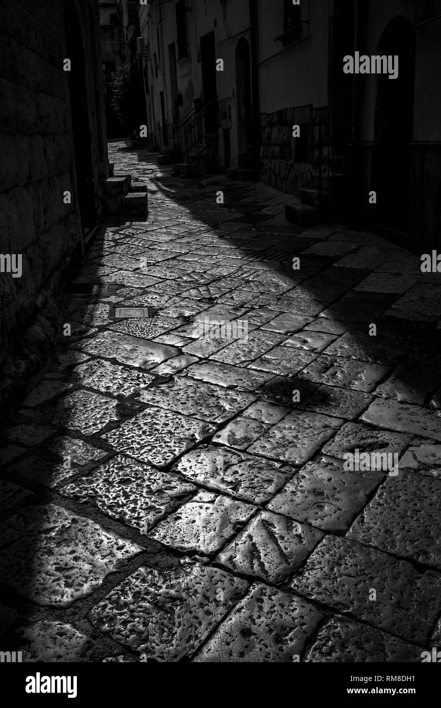Beautiful Sun-lit stone narrow street in Altamura, Apulia, Italy. Black and white high contrast photograph taken against the Sun light in sunny summer afternoon in the old center of the stunning town - Stock Image
