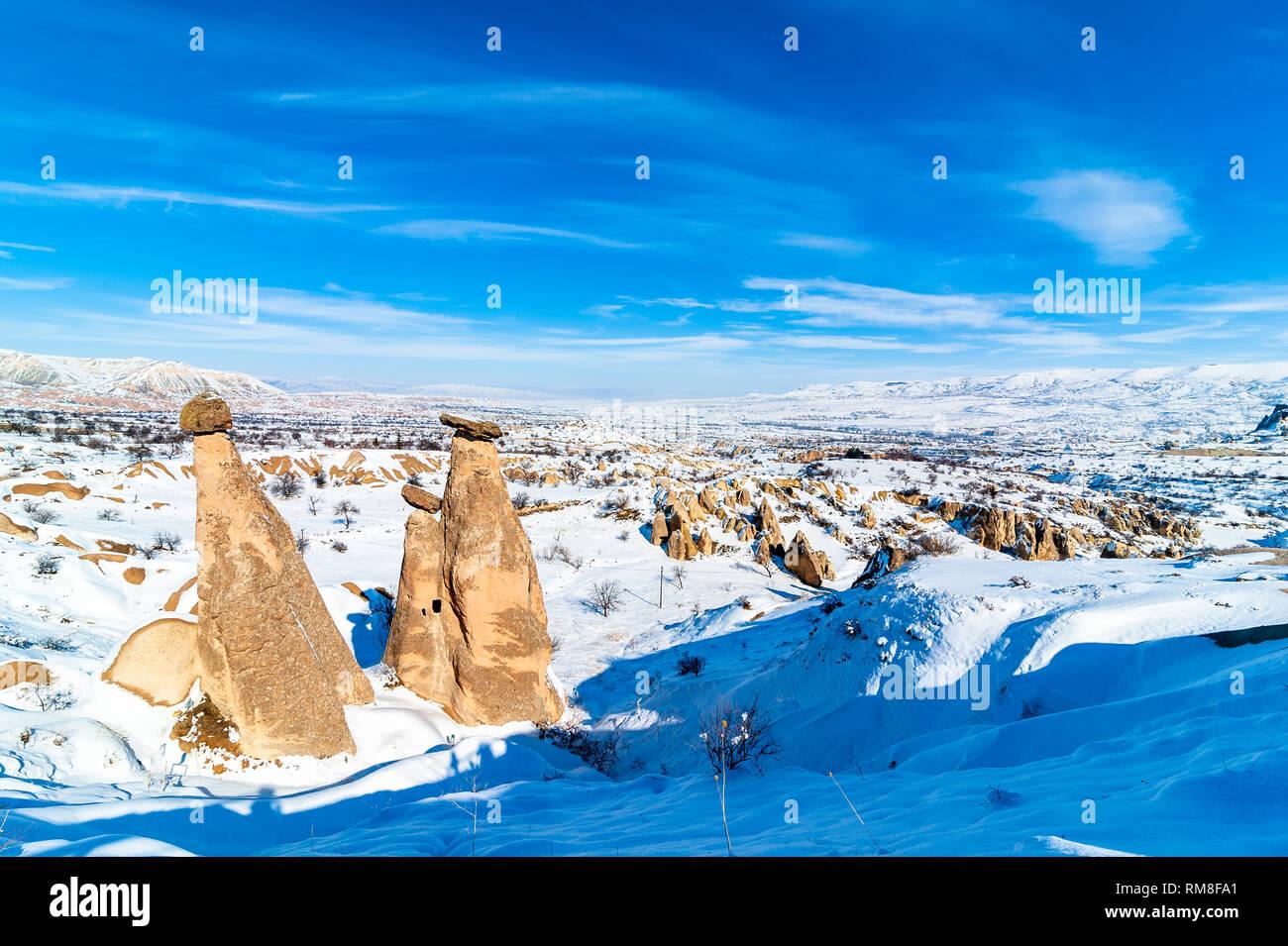 Snowy winter time at three Graces, three Beautifuls (uc guzeller) rock hills in Devrent valley Cappadocia, Nevsehir, Turkey - Stock Image