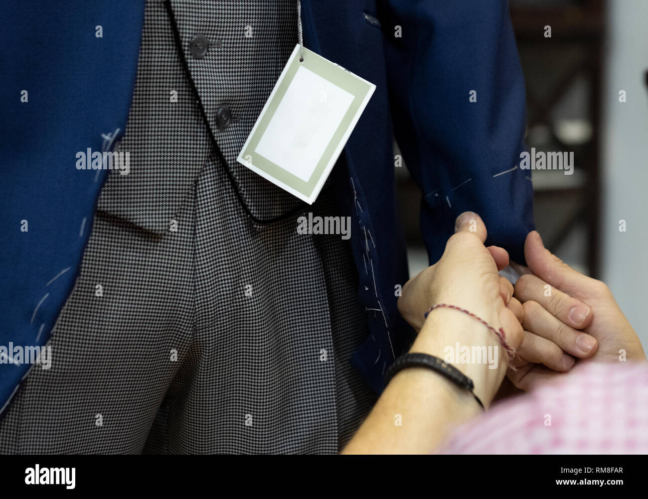 tailor arranging boyfriend suit sleeve in a store - Stock Image