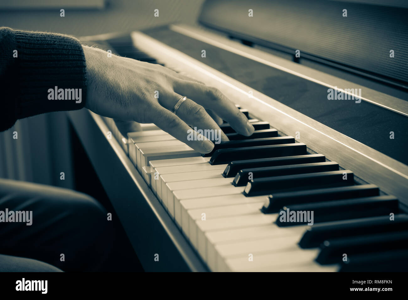 Hands of a man playing the electric piano. - Stock Image