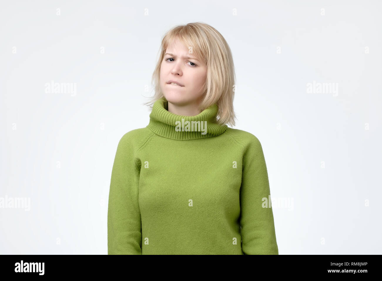 Beautiful young woman with blonde hair biting her lips with thoughtful doubtful expression Stock Photo