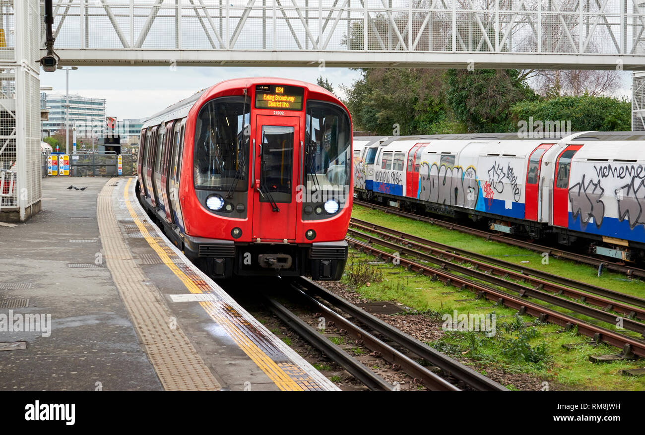 LONDON UNDERGROUND OR TUBE TRAIN  AT A STATION DESTINATION EALING BROADWAY ON THE DISTRICT LINE - Stock Image