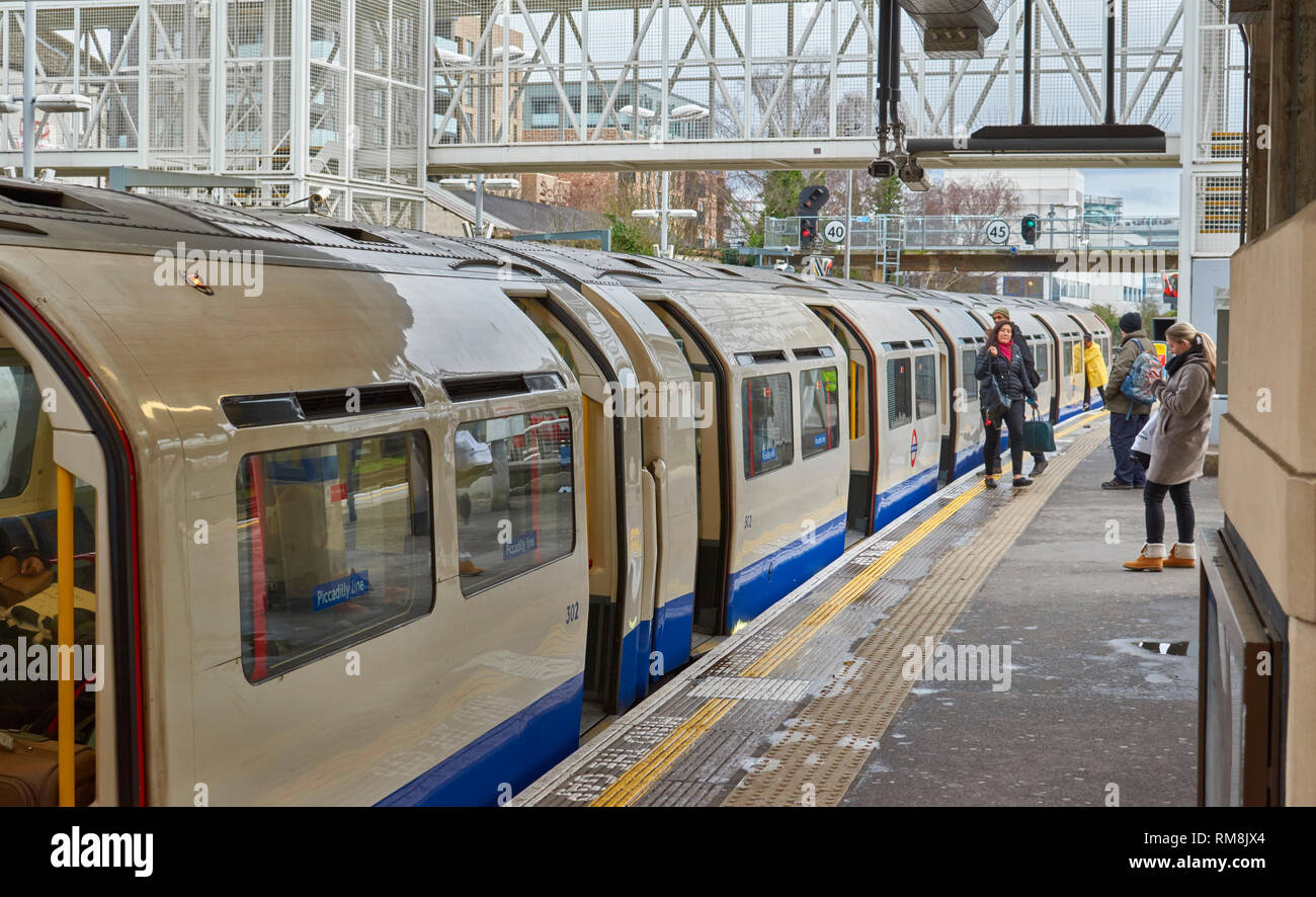 LONDON UNDERGROUND OR TUBE TRAIN  AT A STATION ON PICCADILLY LINE DOORS OPEN AND PASSENGERS - Stock Image