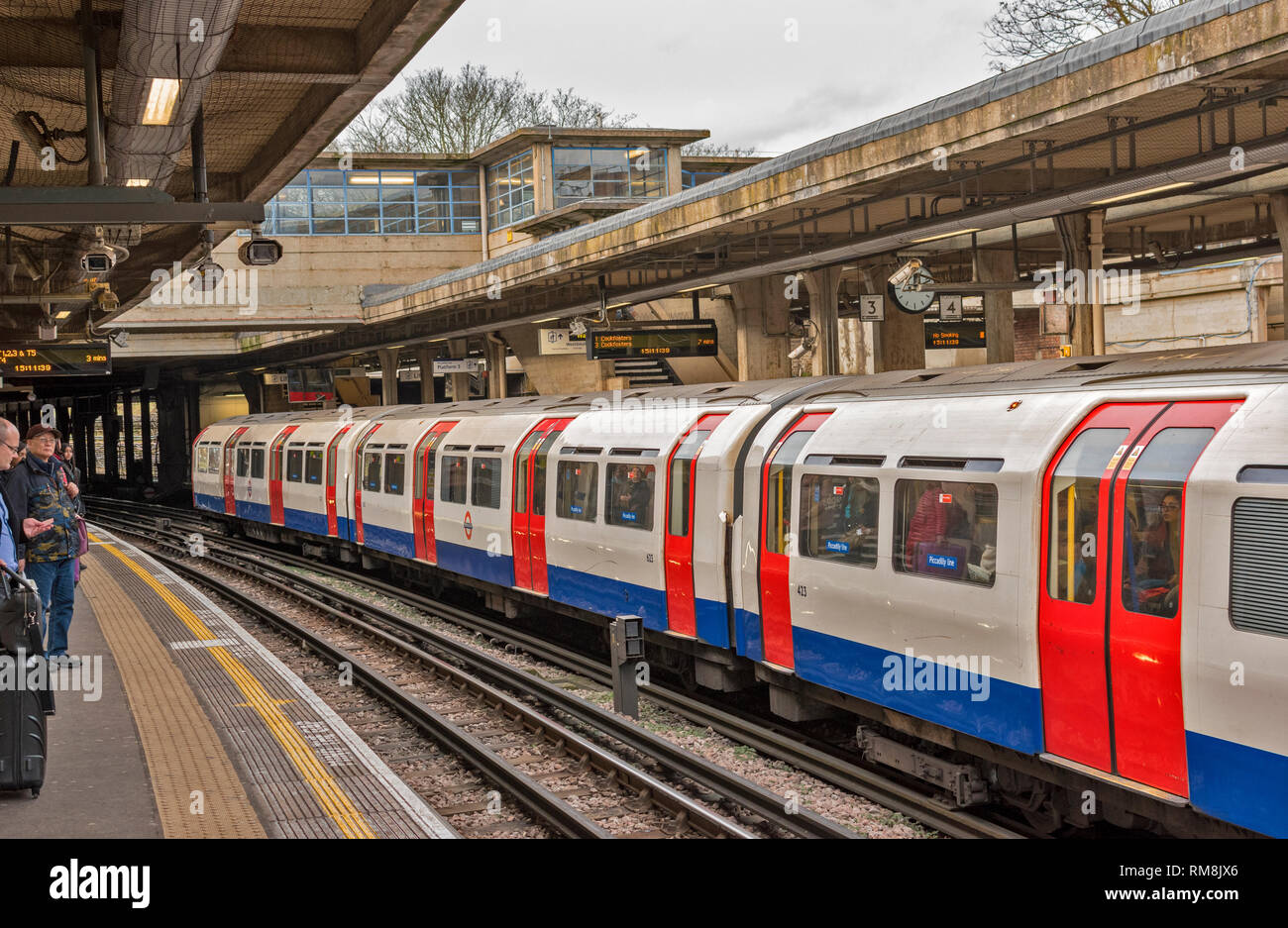 LONDON UNDERGROUND OR TUBE TRAIN ARRIVING AT A STATION ON PICCADILLY LINE WITH WAITING PASSENGERS - Stock Image