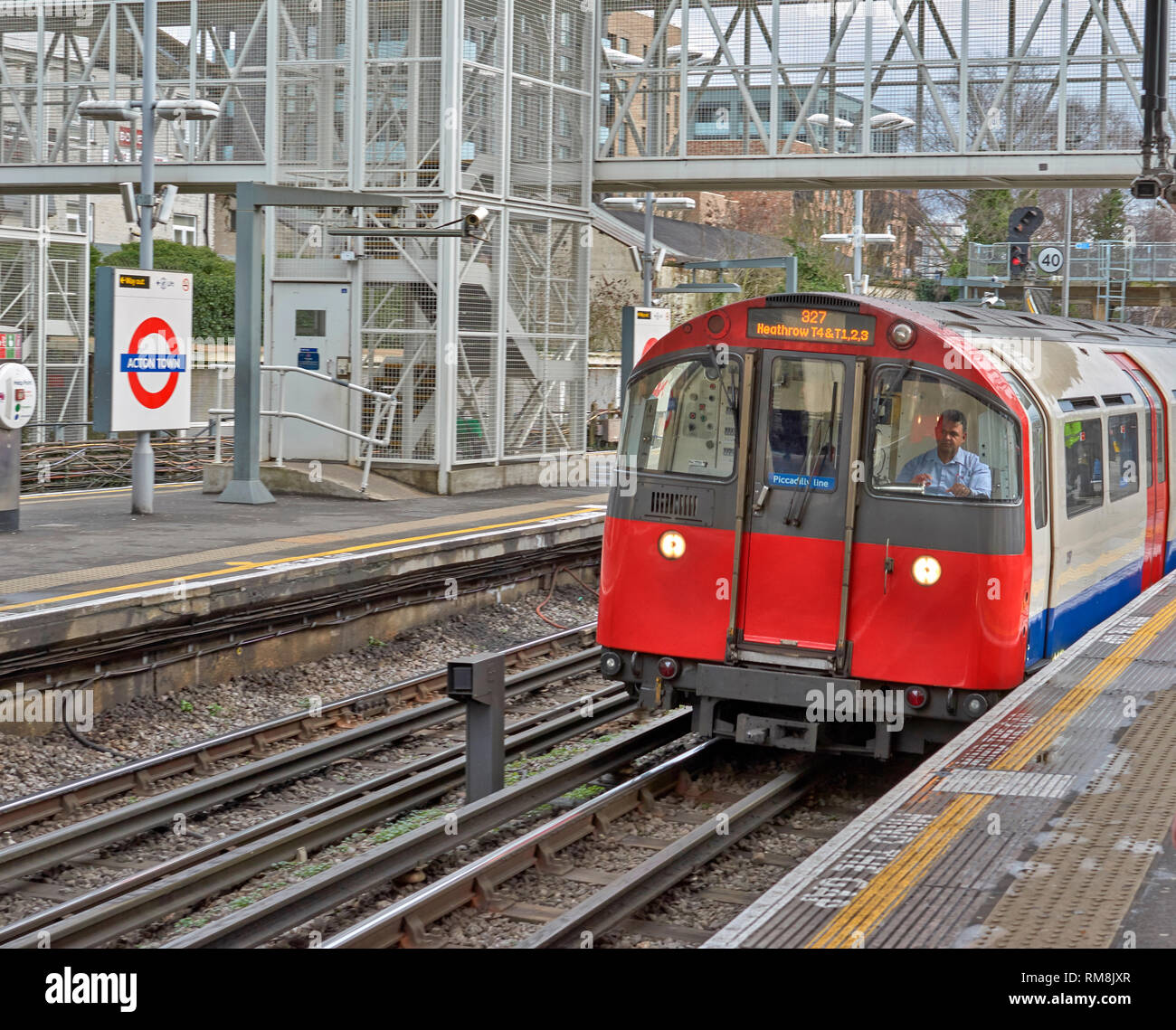 LONDON UNDERGROUND OR TUBE TRAIN ARRIVING AT ACTON TOWN STATION ON PICCADILLY LINE FOR HEATHROW TERMINALS - Stock Image