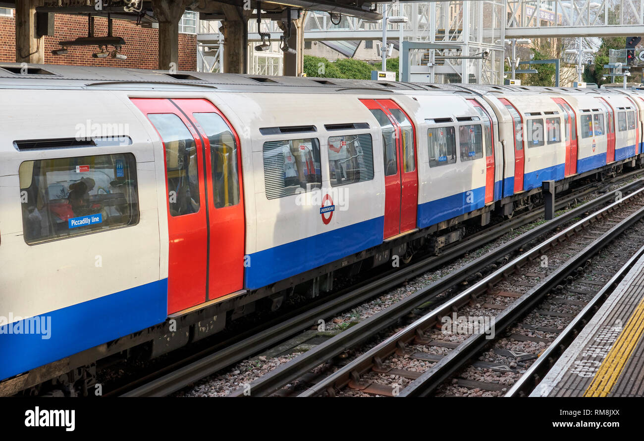 LONDON UNDERGROUND OR TUBE TRAIN ARRIVING AT STATION ON PICCADILLY LINE - Stock Image