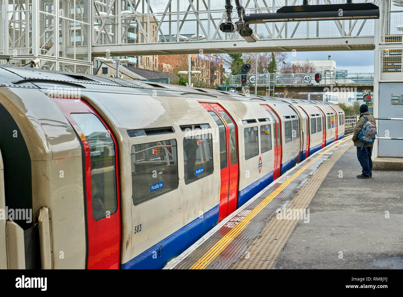 LONDON UNDERGROUND OR TUBE TRAIN PASSENGER WAITNG AT A STATION ON THE PICCADILLY LINE - Stock Image