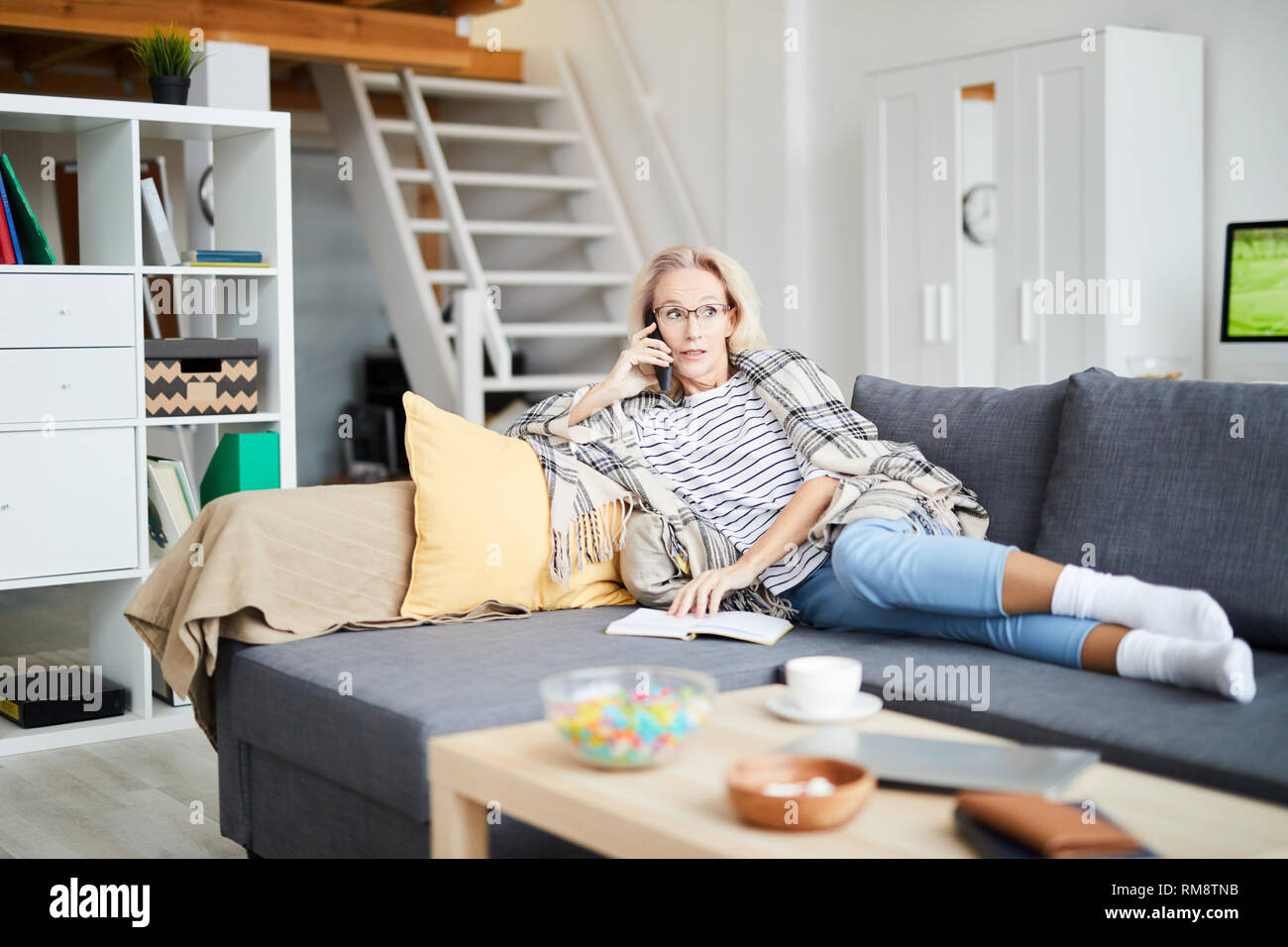 Woman Speaking by Phone at Home Stock Photo