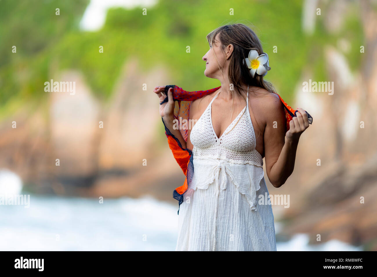 Beautiful slender Italian woman on a pointy rock with the waves coming in on the rocky beach in the background - Stock Image