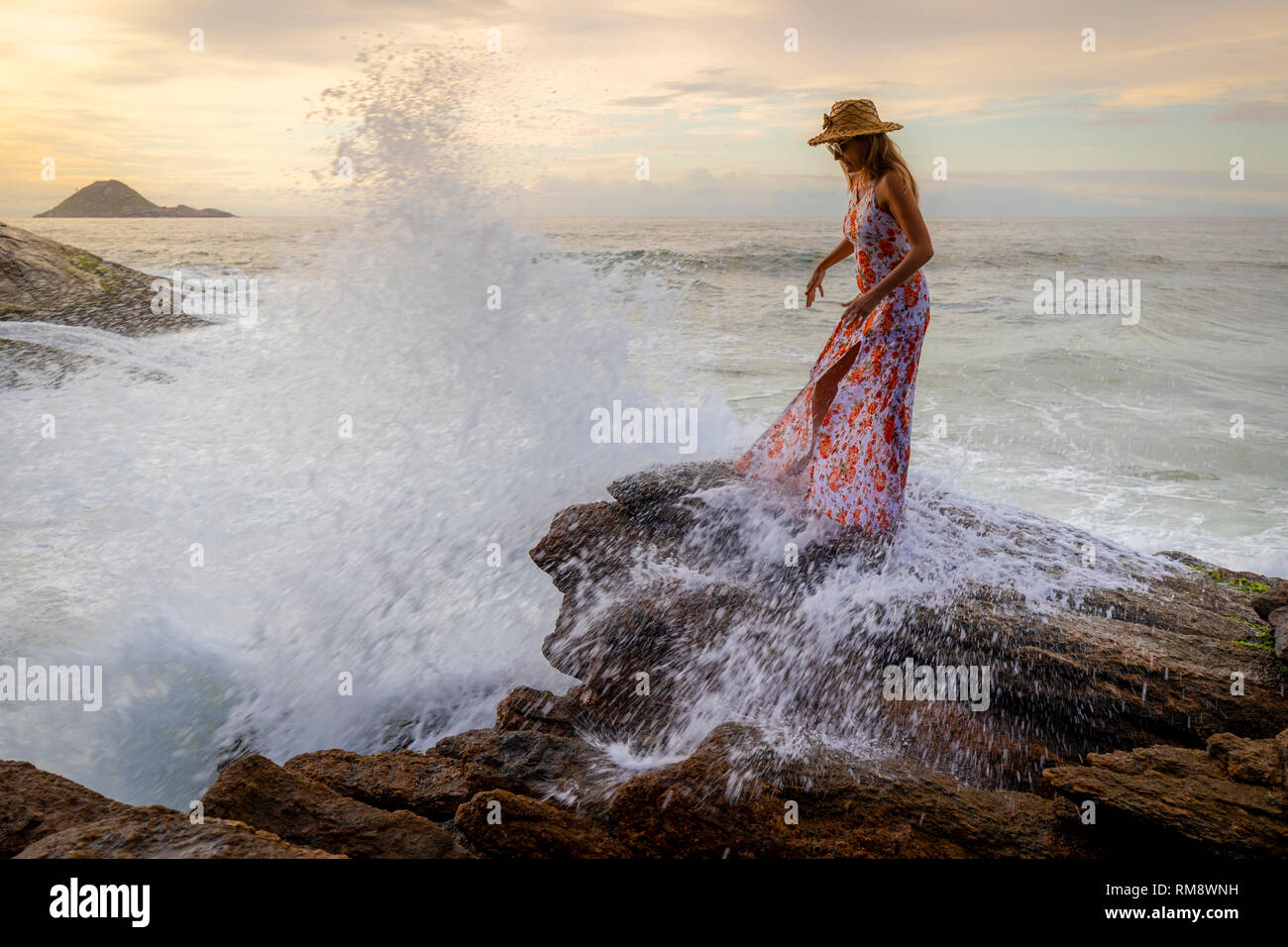 Beautiful slender woman with a hat and stylish dress standing on a rock at a beach where a forceful wave splashes violently around her - Stock Image