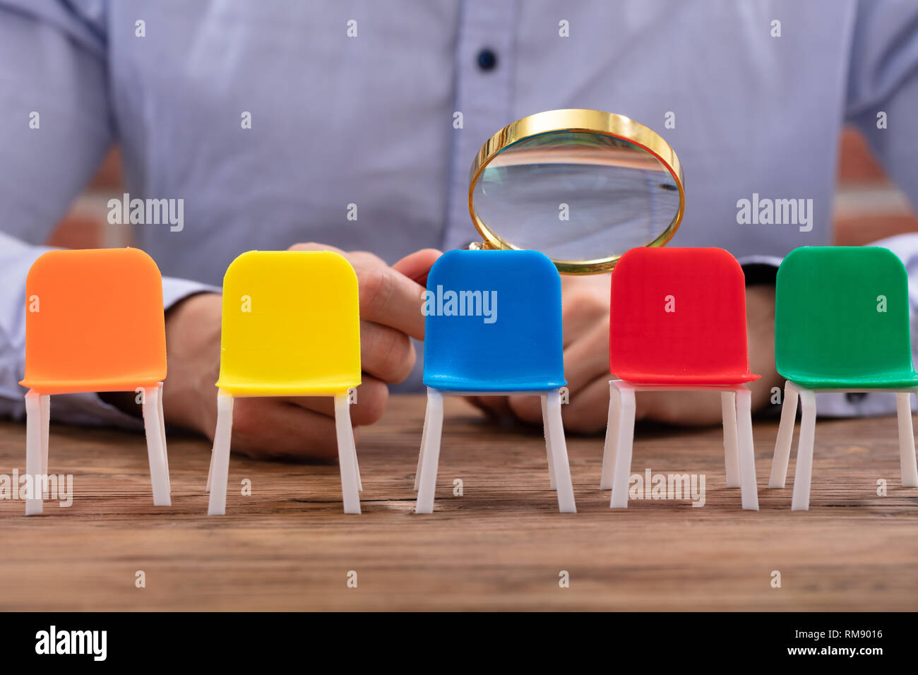 Close-up Of A Businessperson's Hand Looking At Vacant Colorful Chairs Through Magnifying Glass Stock Photo
