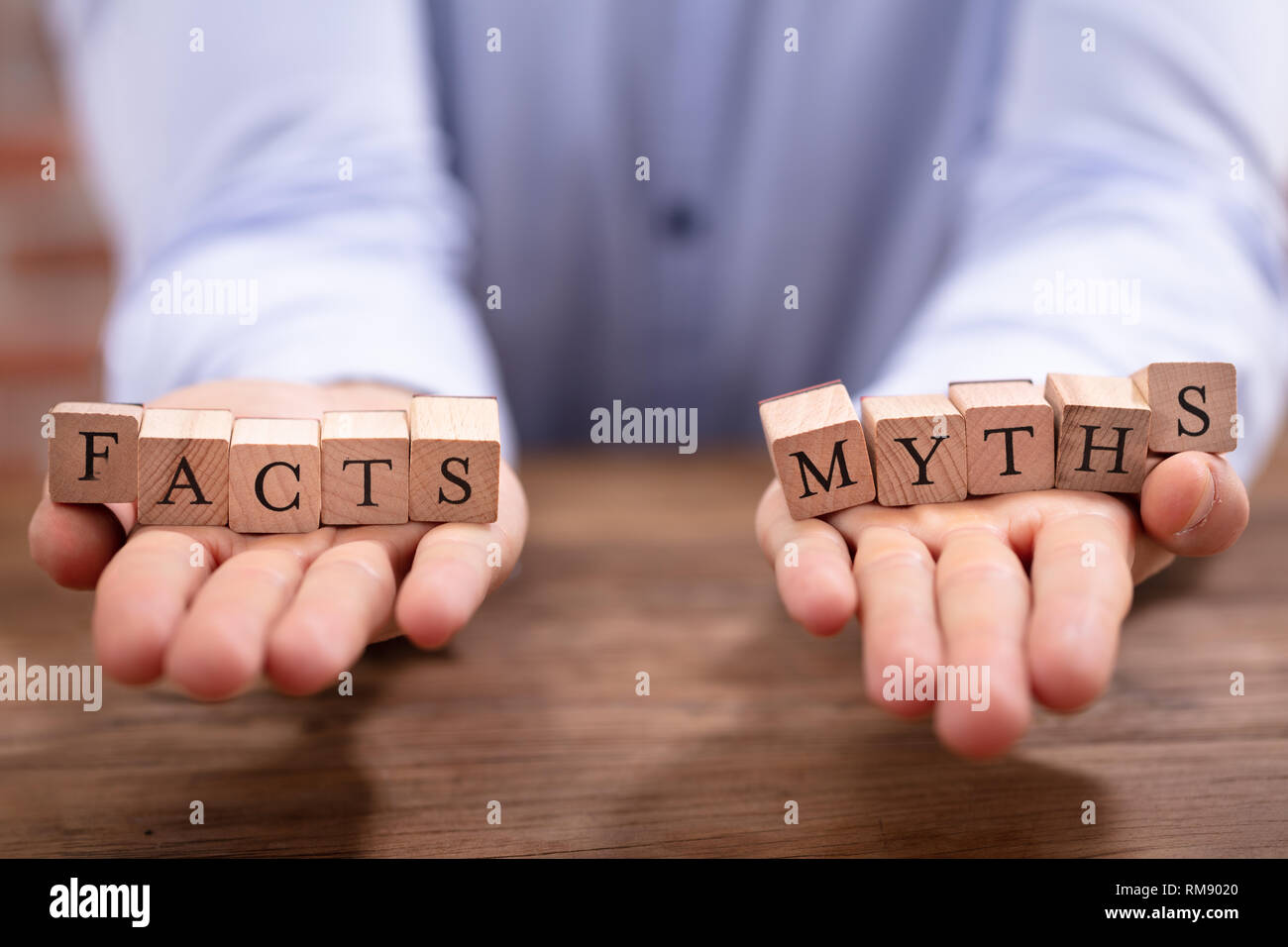 Close-up Businessman's Hand Balancing Facts And Myths Blocks Over Wooden Desk - Stock Image
