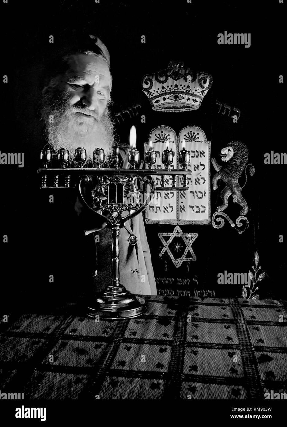 A Chicago rabbi lights Hanukkah candles, ca. 1944. Stock Photo