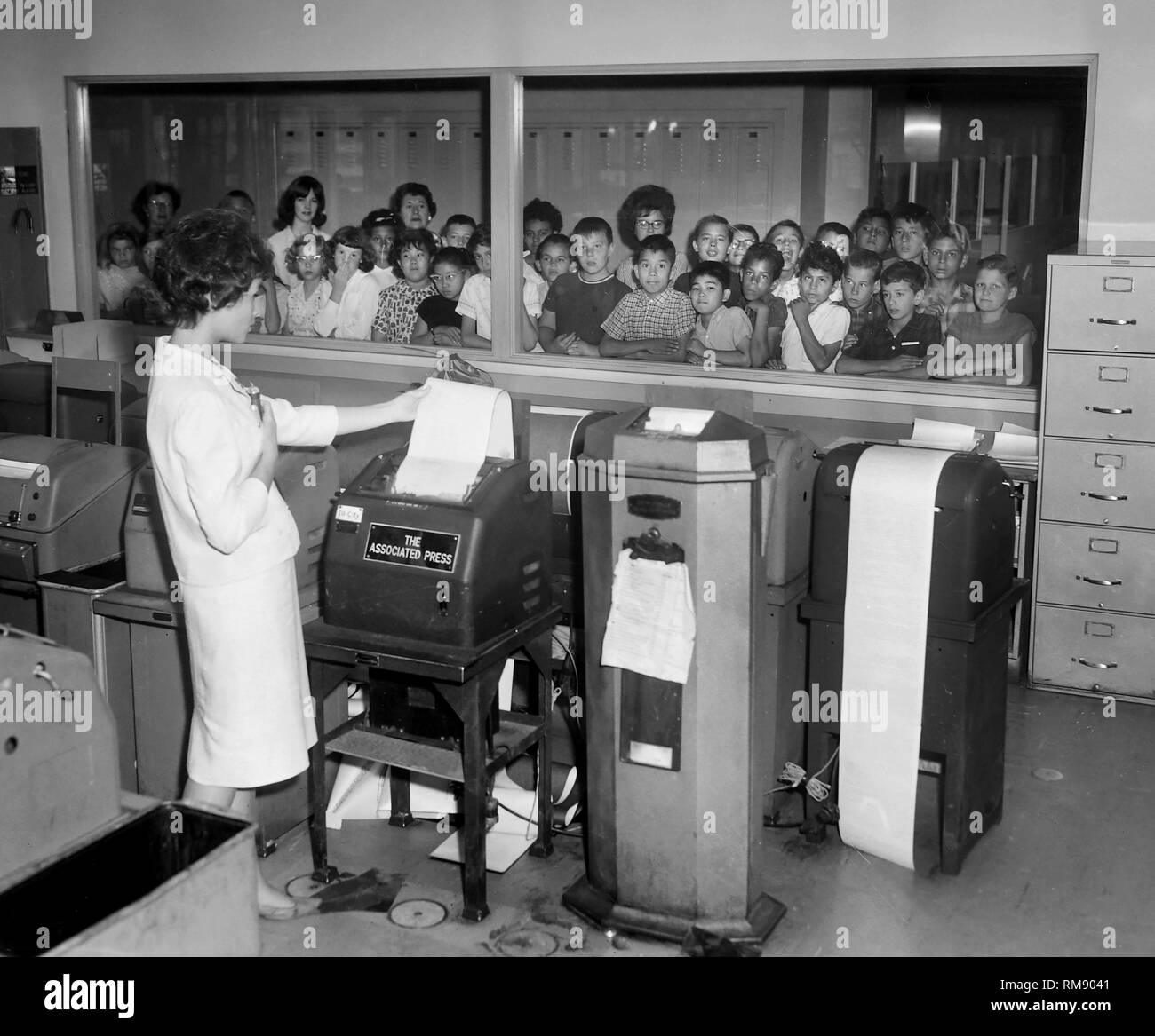 A  touring group of school children on a field trip watch through a window as a woman gathers transmission copy from wire machines for editing in a Chicago newsroom, ca. 1965. - Stock Image