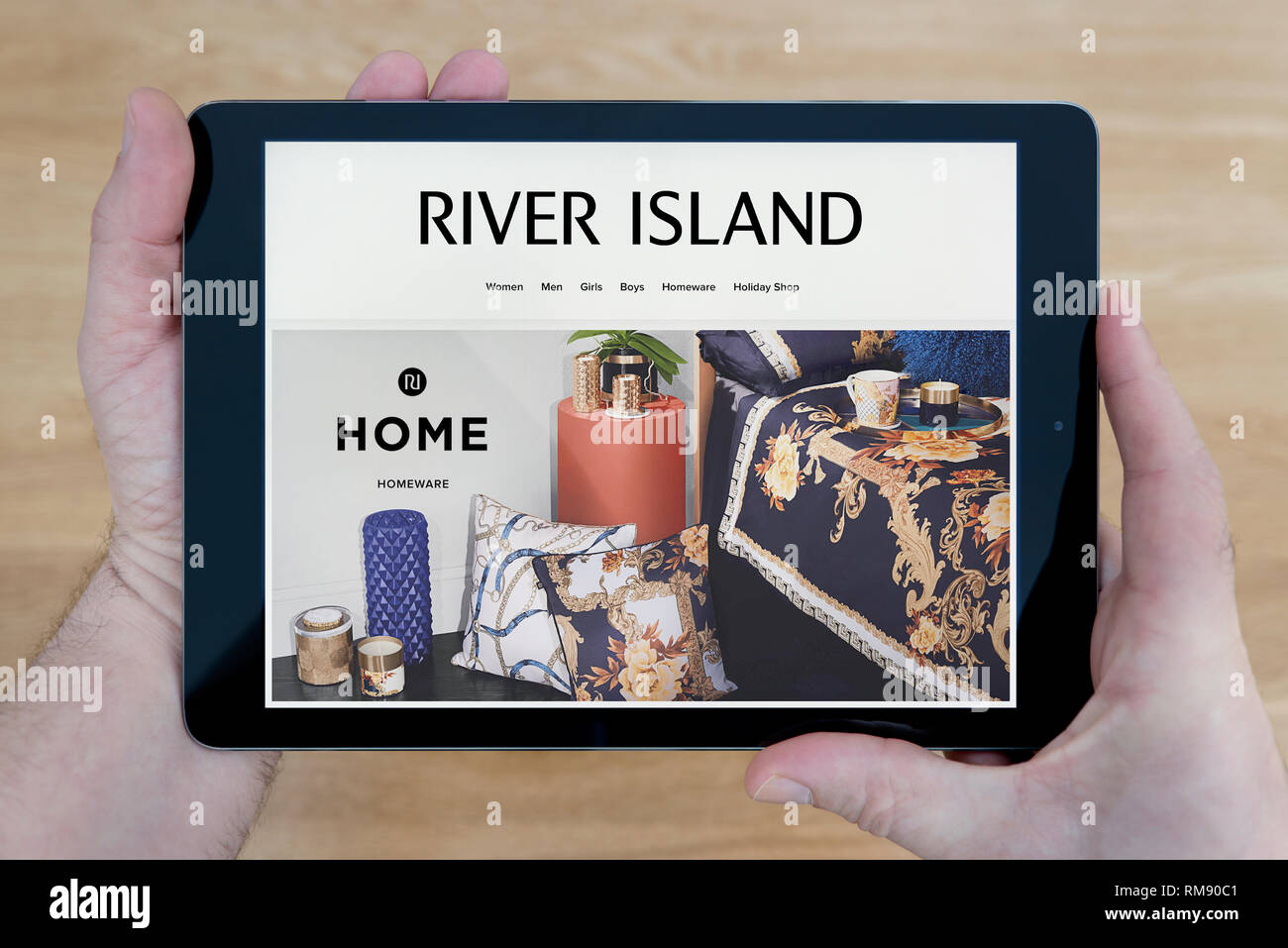 A man looks at the River Island website on his iPad tablet device, shot against a wooden table top background (Editorial use only). Stock Photo