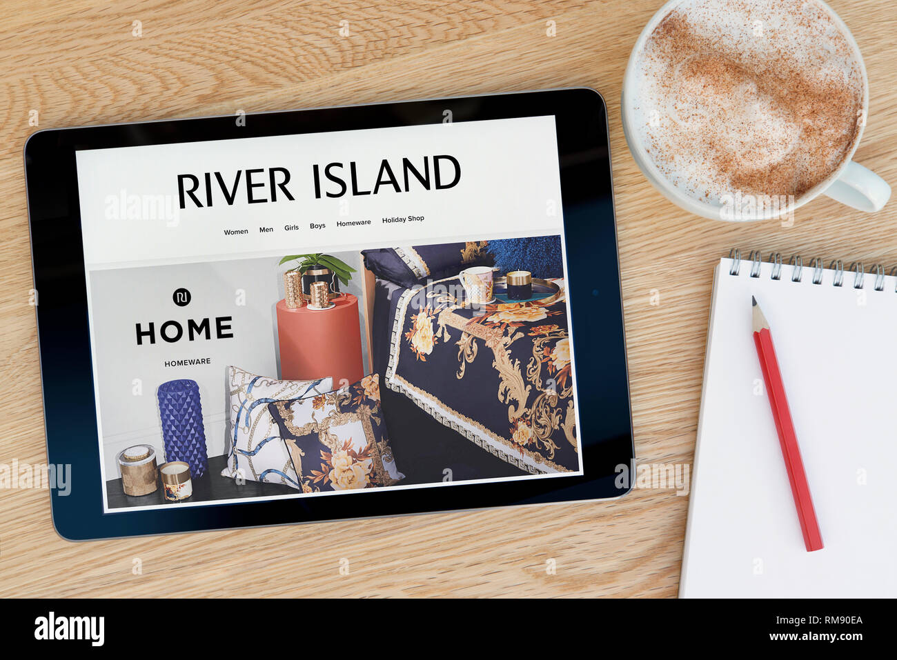 The River Island website features on an iPad tablet device which rests on a wooden table beside a notepad (Editorial use only). Stock Photo