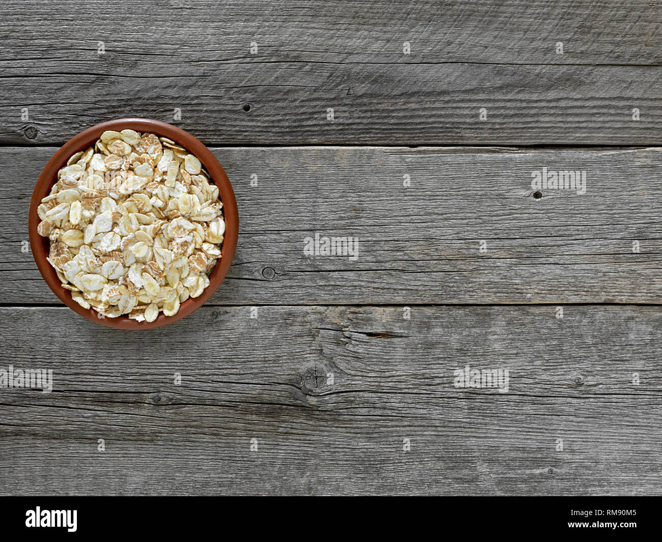Cereal flakes in brown plate on table out of grey boards. Stock Photo