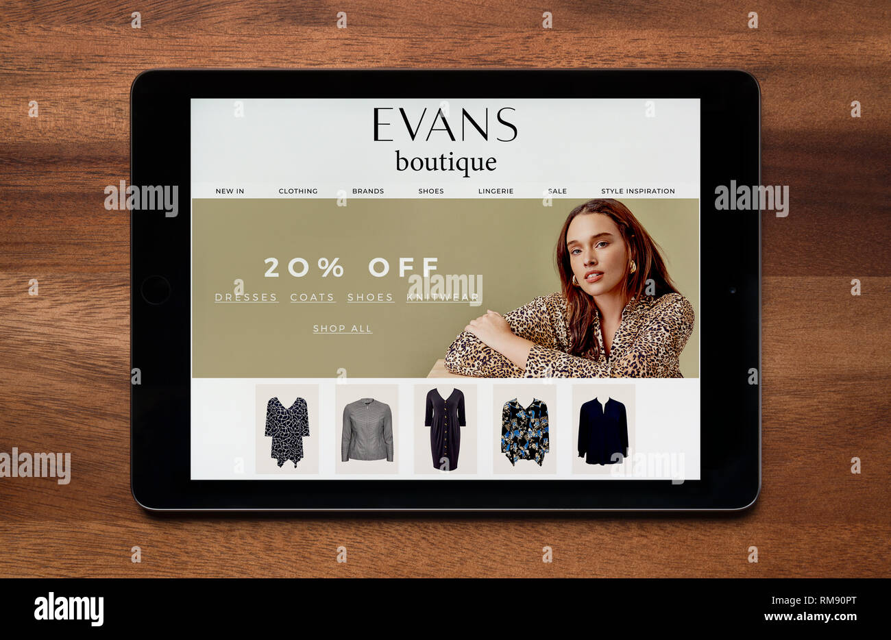 The website of Evans Boutique is seen on an iPad tablet, which is resting on a wooden table (Editorial use only). - Stock Image